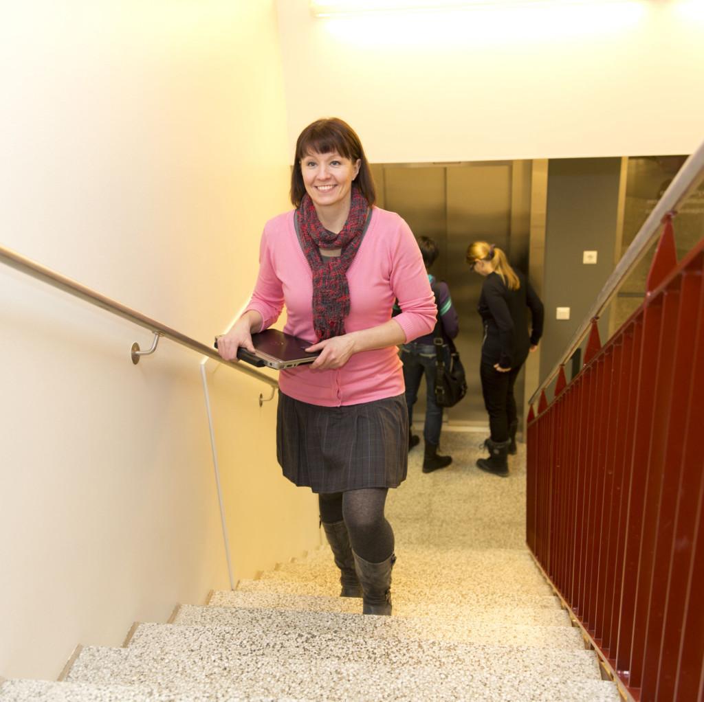 Nainen nousee portaita läppäri käsissään