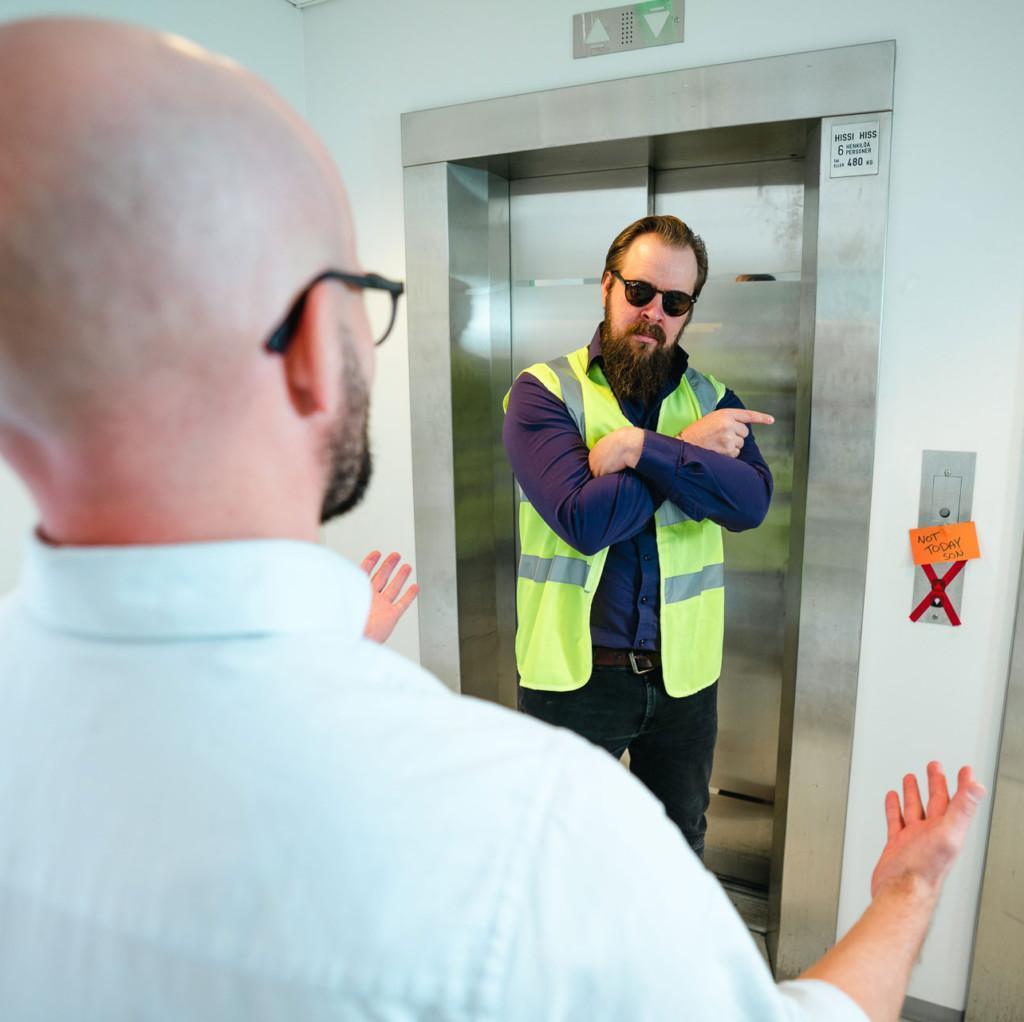 Kuvassa toinen mies seisoo hissin oven edessä huomioliivi päällään ja estää kuvassa etualalla olevaa miestä menemästä hissiin.